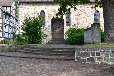 Die 1959 eingerichtete Gedenkstätte vor der Niederkaufunger Kirche mit dem Mahnmal für die Toten des II. Weltkriegs, dem Denkmal für die Gefallenen des I. Weltkriegs und der Friedenseiche von 1871 (Zustand 2012)
