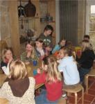 Kinder einer Geburtstagsfeier im Museum sitzen am Kaffeetisch