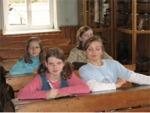Die Teilnehmer des Kindergeburtstag sitzen auf einer alten Schulbank